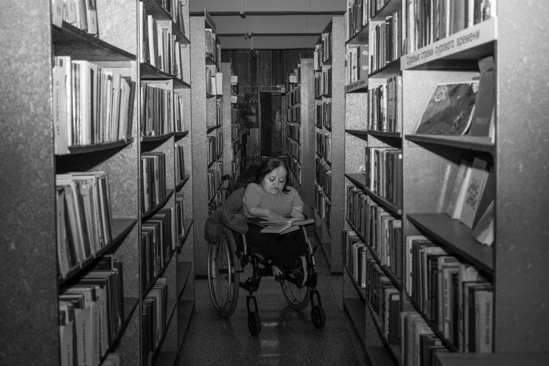 Оля выбирает книги в библиотеке