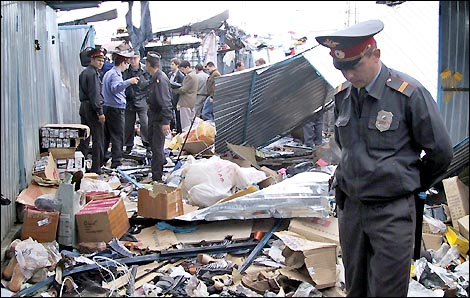 Investigators work at the site of a bomb explosion at a market
